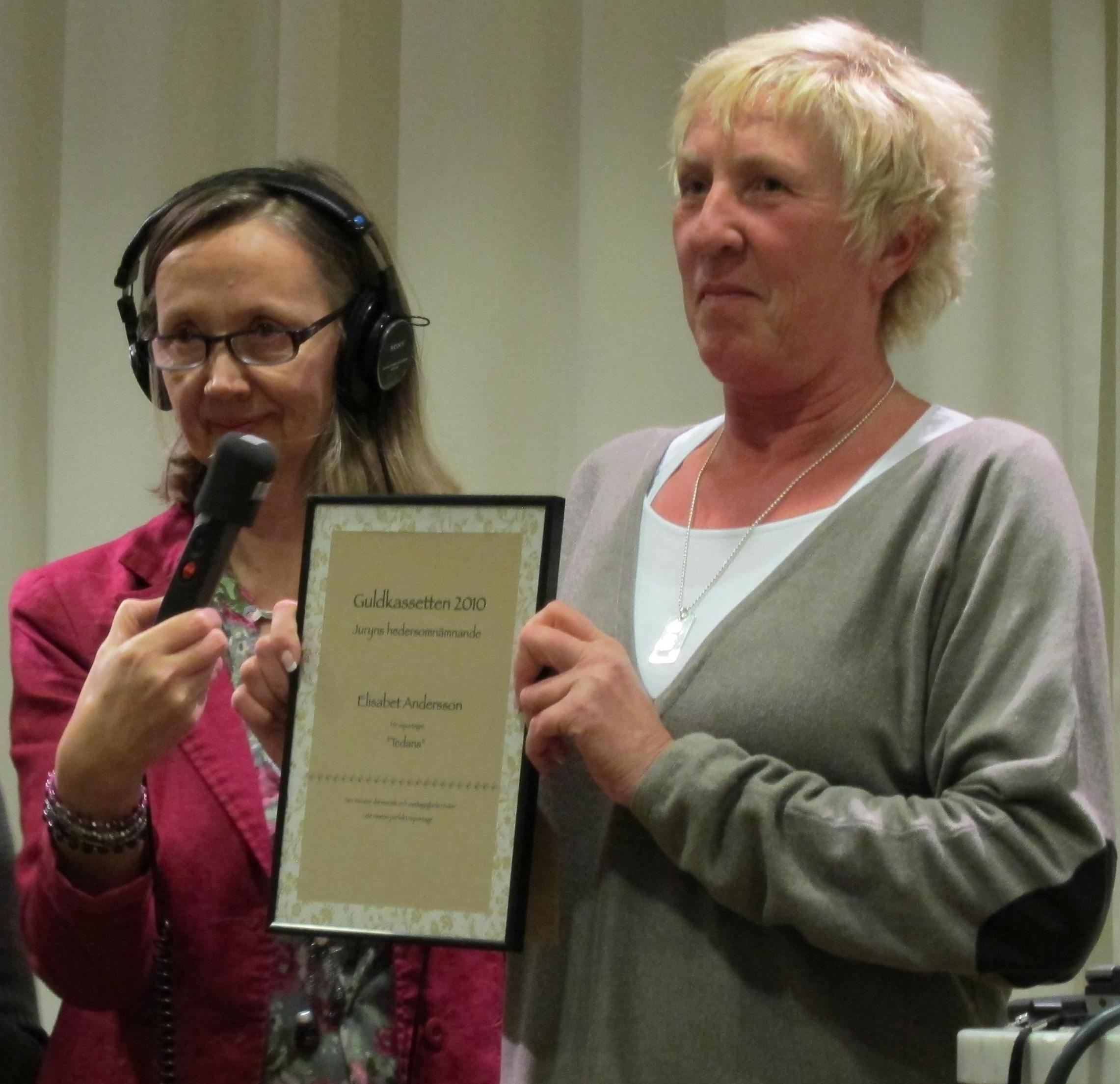 Elisabet Andersson visar upp sin plakett, medan Åsa Nilsson bandar prisutdelningen. Foto: Martin Holmström
