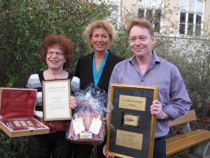 Johan Rosengren till höger, Birgitta Fredén till vänster, båda med sina pristavlor. I mitten prisutdelare Lena Liljeborg.