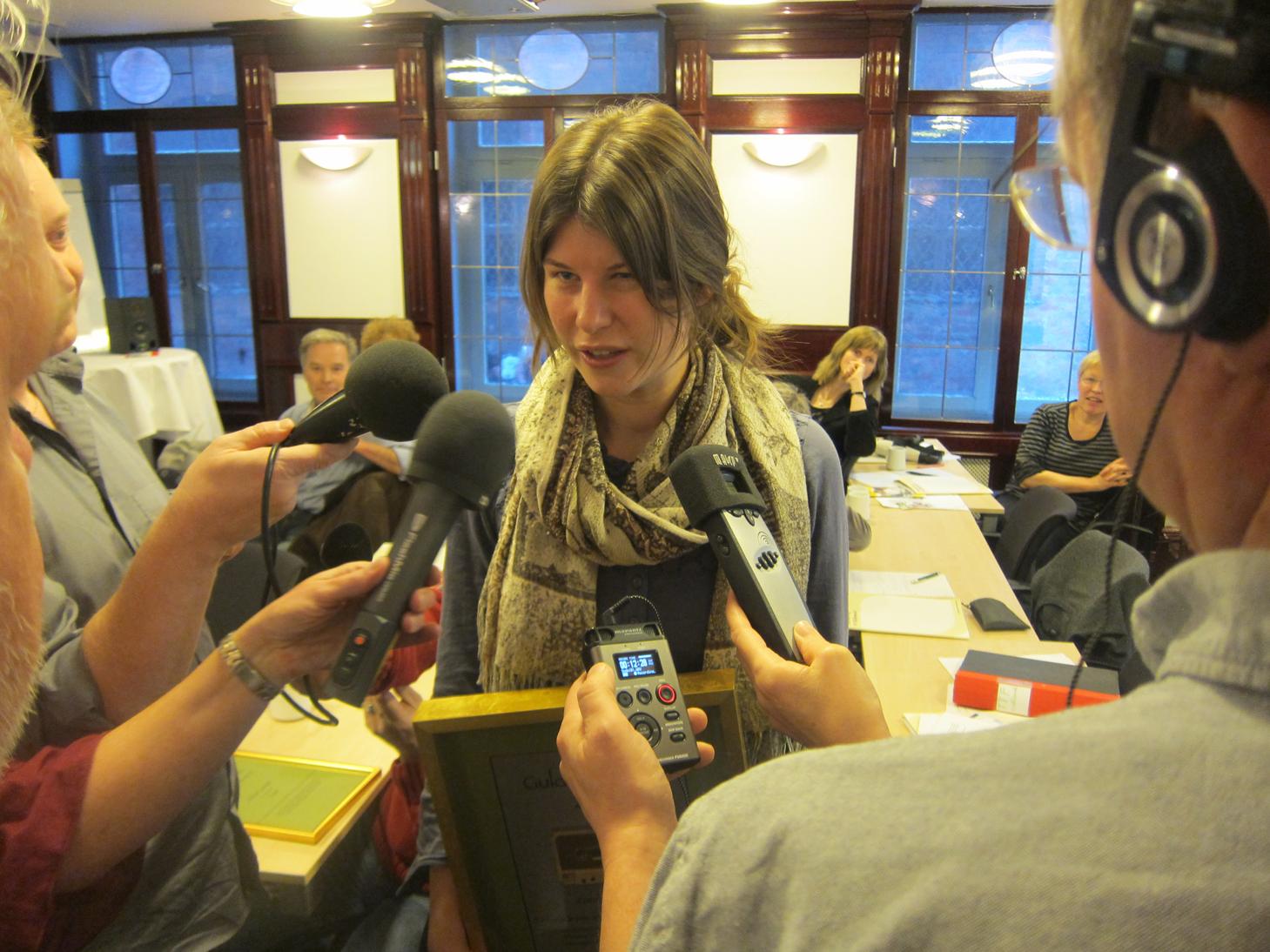 """Zandra Classon, vinnare av Guldkassetten 2012, berättar med fyra mikrofoner framför sig om sitt vinnande reportage """"Det smakar som att hänga ut tungan i regnvädret"""". Zandra är lång och smal, hon har brunt hår i mittbena och en sjal löst lindad om halsen."""