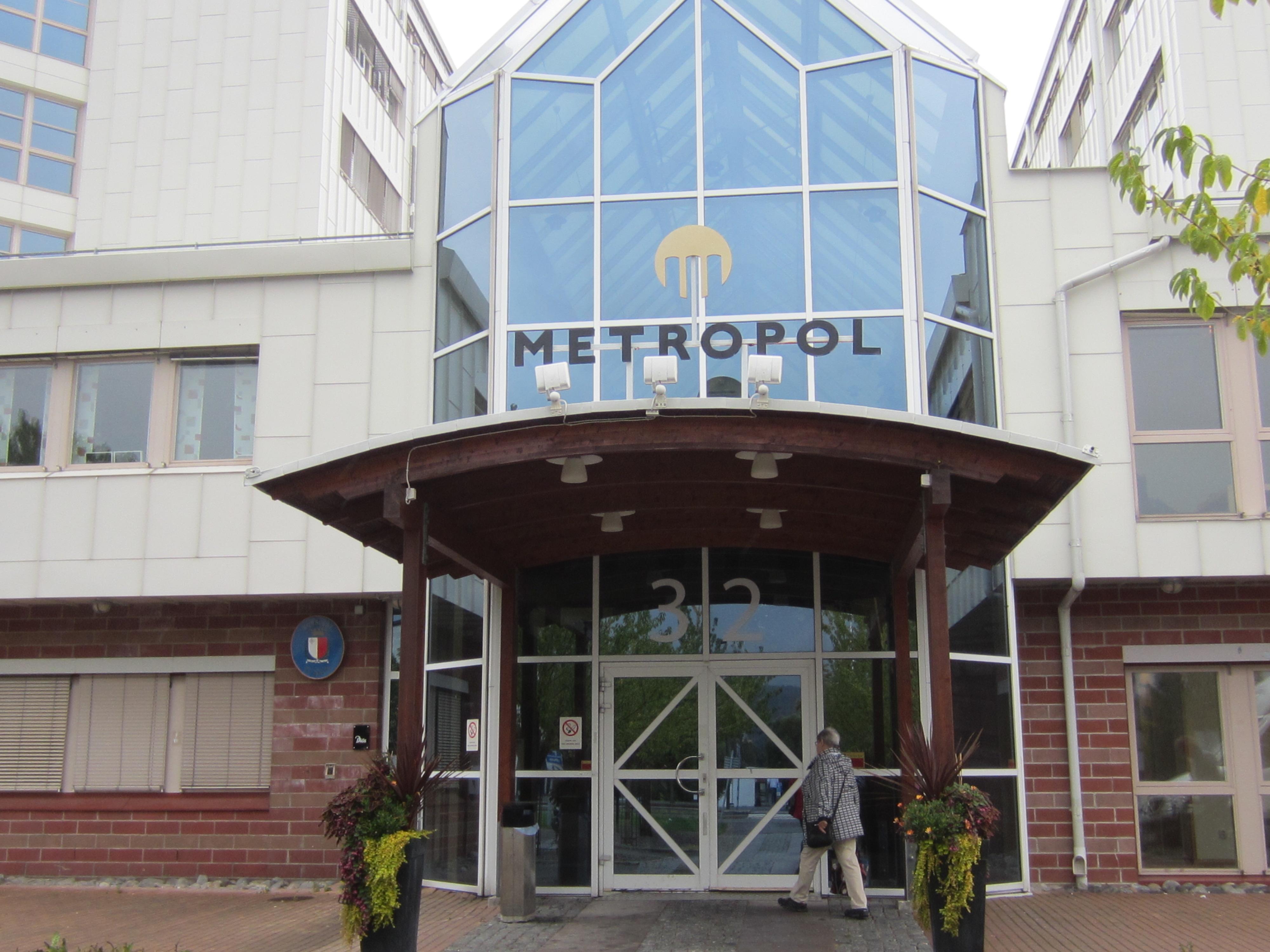 Metropolhusets entré med glasdörrar och en glashall innanför.