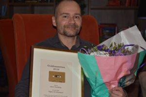 Vinnaren av Guldkassetten 2016, Mats Sundling, sitter leende i en röd fåtölj. I händerna håller han upp pristavlan, med en förgylld kassett, och en fin blomsterbukett.
