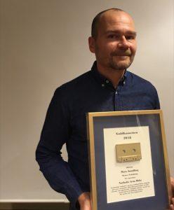 En glad Mats Sundling, i blå skjorta, poserar med den inramade Guldkassetten.