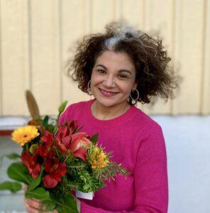 En leende Aziza Dhaouadi iförd cerise tröja och med en färgglad blombukett i handen.