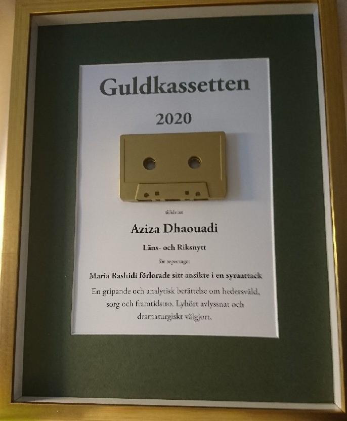 """Närbild på pristavlan. En ram i guldfärg, mörkgrön passepartout och svart text på vit botten med texten """"Guldkassetten 2020"""" överst. Under texten sitter ett guldfärgat kassettband, och under det står Aziza Dhaouadi och juryns motivering."""