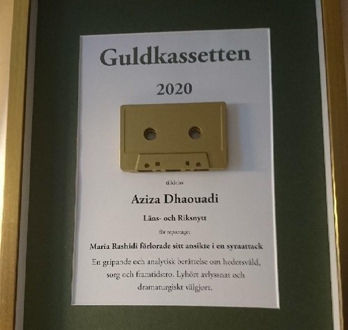"""Närbild på pristavlan. Ram i guldfärg, mörkgrön passepartout och svart text på vit botten. Överst står det """"Guldkassetten 2020"""". Under texten sitter en guldfärgat kassettband, och under det står det """"Aziza Dhaouadi"""" och juryns motivering."""